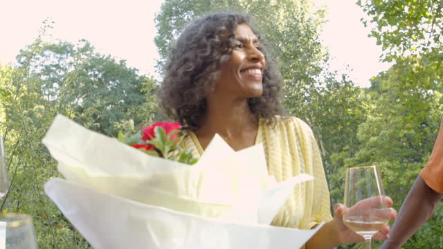 a woman accepts a gift of flowers - wine glass stock videos & royalty-free footage