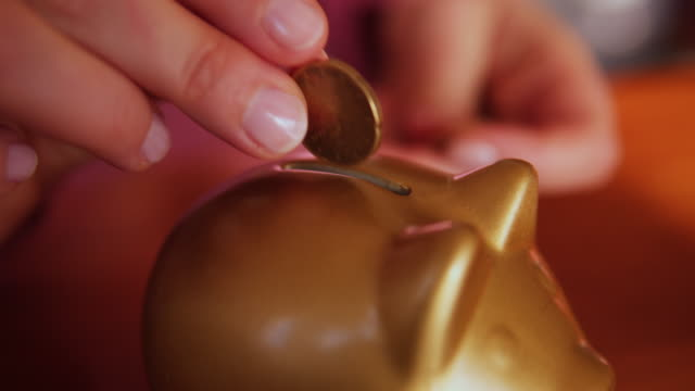 woman adding a coin to savings in a piggy bank. - currency symbol stock videos & royalty-free footage