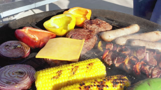 a woman adding cheese to hamburgers on a grill loaded with delicious meats and vegetables - cheeseburger stock videos & royalty-free footage