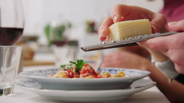 woman adding cheese with a grate to pasta - garnish stock videos & royalty-free footage