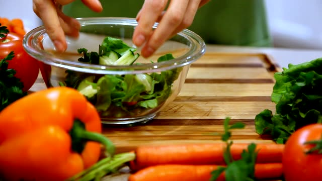 woman adding chopped vegetables to salad bowl. - carving knife stock videos and b-roll footage