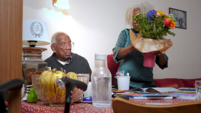 woman adding flowers to a vase for her 91 year old father - fruit bowl stock videos & royalty-free footage