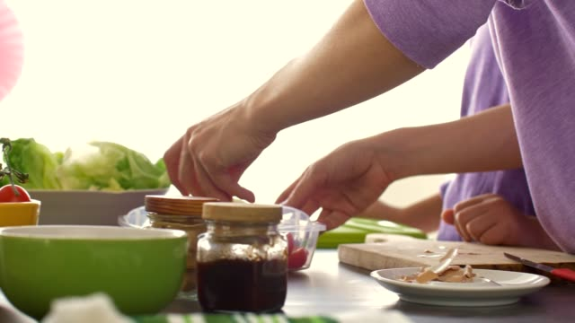 woman adding fresh vegetables to her daughter's school lunch box - lunch stock videos & royalty-free footage
