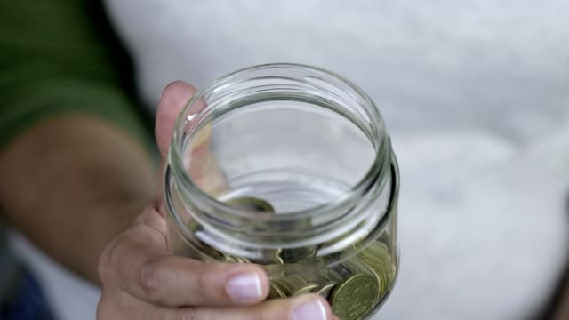 woman adding one euro into savings in jar - european union coin stock videos & royalty-free footage