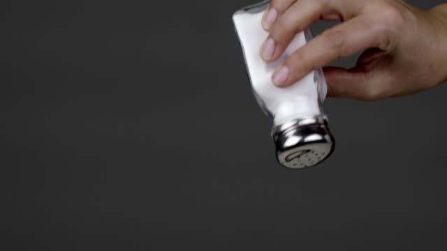 woman adding salt on food via salt shaker - sprinkling stock videos & royalty-free footage