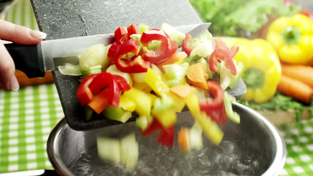 woman adds chopped vegetable in hot water - sprinkling stock videos and b-roll footage