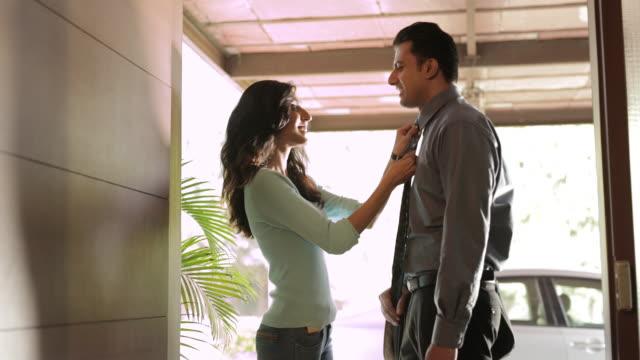 vídeos y material grabado en eventos de stock de ms woman adjusting boyfriend's necktie at doorway / india - adios