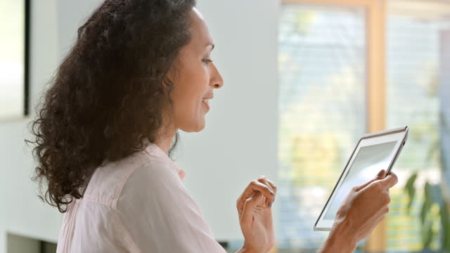 woman adjusting setting on her tablet to control her smart home - adjusting stock videos and b-roll footage