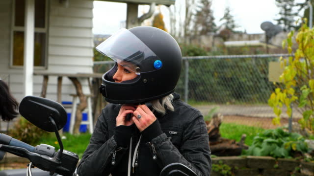woman adjusting strap on motorcycle helmet before ride - ヘルメット点の映像素材/bロール