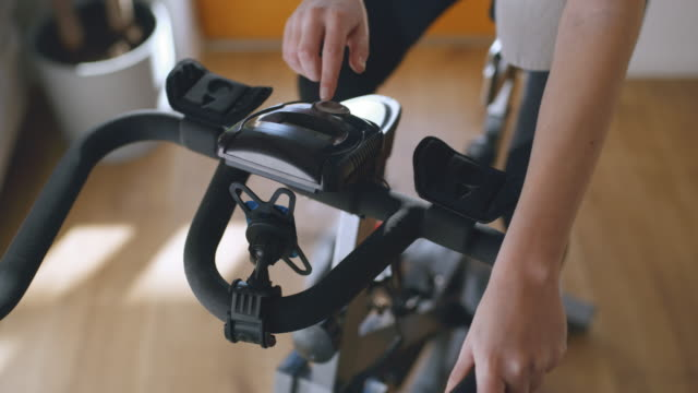 slo mo woman adjusting the exercise bike - home workout stock videos & royalty-free footage