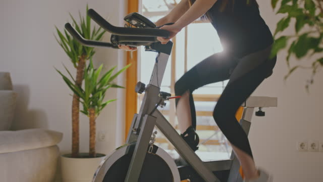 slo mo woman adjusting the exercise bike - exercise bike stock videos & royalty-free footage
