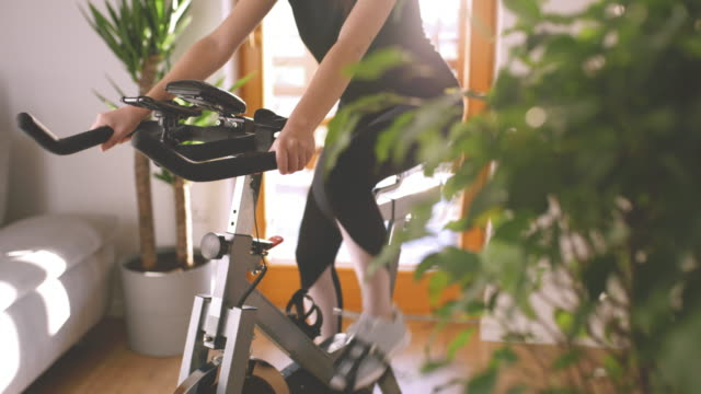 slo mo woman adjusting the exercise bike while cycling on it - exercise bike stock videos & royalty-free footage