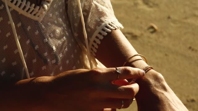 woman adjusts bracelets on tahiti beach at sunset, close up - tahiti stock videos & royalty-free footage