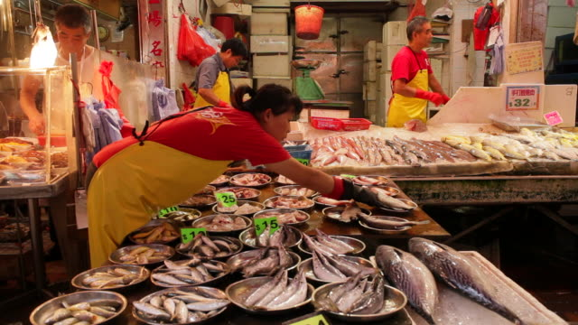 A woman adjusts plates of fish on a table.