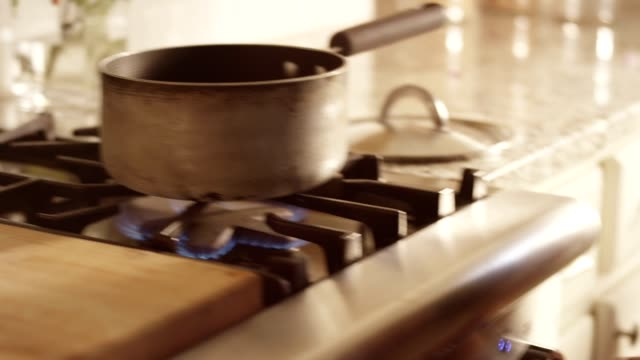 vídeos y material grabado en eventos de stock de woman adjusts pot on stove, turns dial to adjust flame, examines stovetop. - examen
