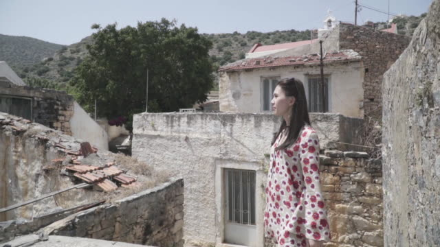 woman admires mountain town in greece, pan right - 手をかざす点の映像素材/bロール