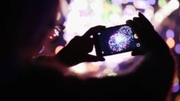 A woman admires the fireworks in the night sky. Take pictures with your smartphone. 4k 10 bit video