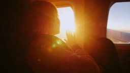 A woman admires the sunrise from the window of the plane. Touches her hand to the orange rays