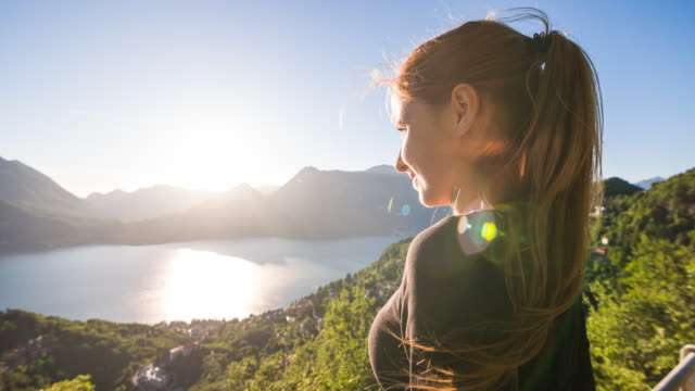 Woman admiring breathtaking view standig above Italian lake