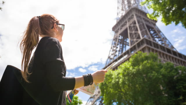 woman admiring eiffel tower while walking the streets of paris on a sunny day - admiration stock videos and b-roll footage