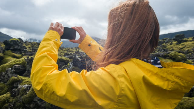 woman admiring rocky and mossy landscape of iceland - raincoat stock videos & royalty-free footage