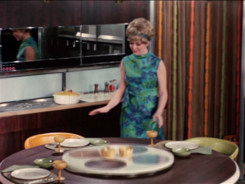 1968 woman admiring table in automated futuristic kitchen / industrial - prelinger archive video stock e b–roll