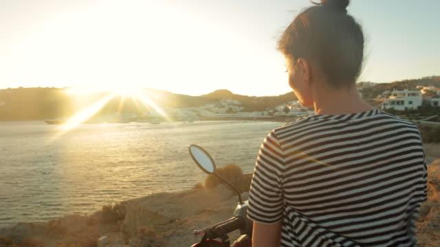 stockvideo's en b-roll-footage met vrouw bewonderen van het zeegezicht op de motor-scooter. - scooter