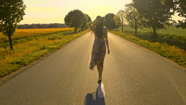 ms tu ws slo mo woman admiring the sunset on a country road - wonderlust stock videos & royalty-free footage