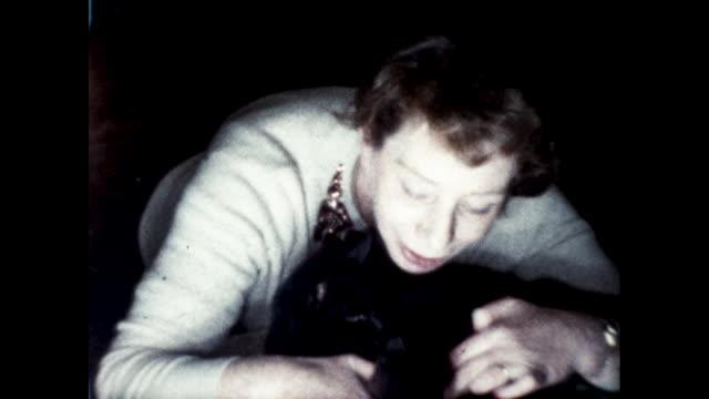 woman affectionately kneeling on the carpet and petting a black cat - 黒猫点の映像素材/bロール