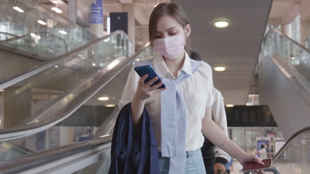 woman aged 20-30 uses a mobile phone while at the airport during their flight to check-in at the counter. - businesswoman stock videos & royalty-free footage