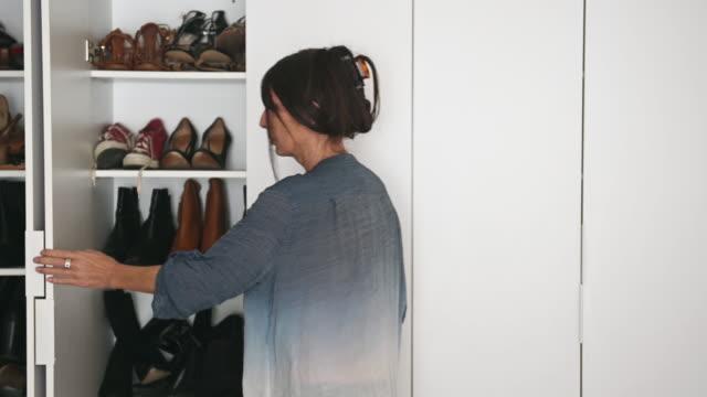 vídeos de stock e filmes b-roll de woman alone arranging many shoes in large wardrobe - closet