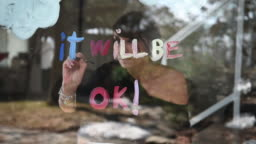 Woman Alone Home Drawing Covid-19 Rainbow symbol on Hallway Window