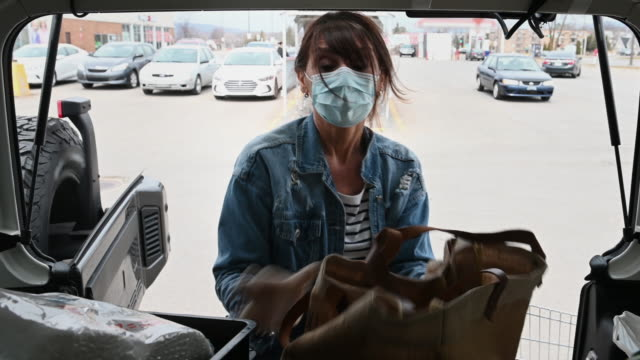 woman alone packing car trunk with grocery bag wearing mask and gloves - one mature woman only stock videos & royalty-free footage