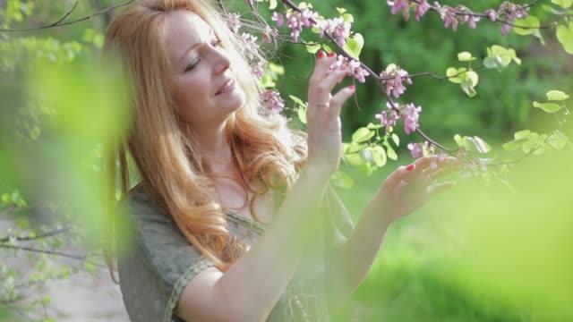 vidéos et rushes de femme parmi les branches de fleurs - 40 44 ans