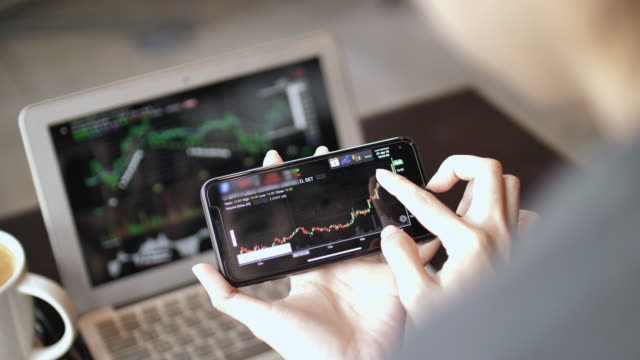 woman analyzing stock market data on smart phone - analysing stock videos & royalty-free footage