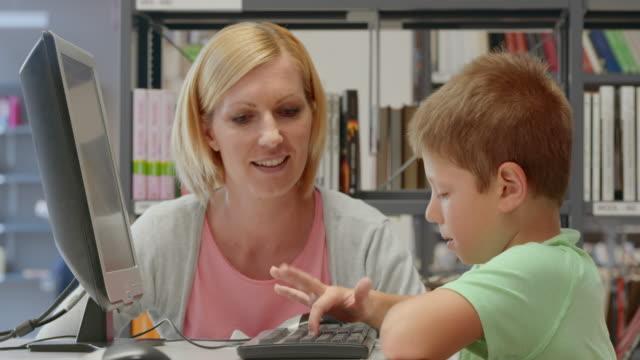 ds 女性と若いコンピューターでネットサーフィンをライブラリー - 公共図書館点の映像素材/bロール
