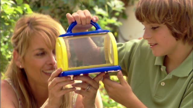 A woman and a boy look at a bug in a bug cage.