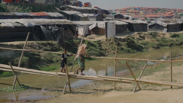 A woman and a child carefully make their way across a makeshift bridge of a few bamboo branches in Kutupalong refugee camp in Bangladesh Fleeing...