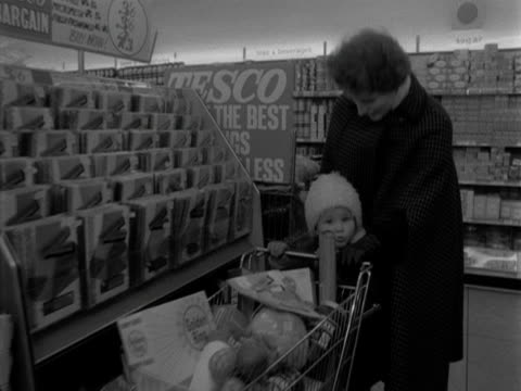 woman and a child shop in a tesco supermarket. 1963. - frozen food stock videos & royalty-free footage