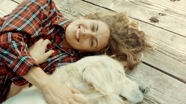 frau und ein hund liegend auf pier am see - moving down stock-videos und b-roll-filmmaterial