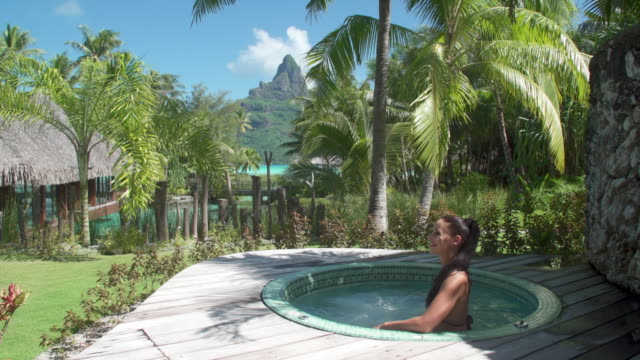 A woman and a hot tub jacuzzi spa, lifestyle at a tropical island resort.