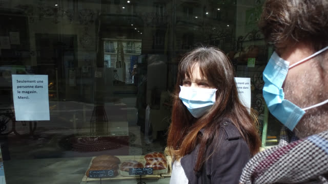 woman and a man, with a protective mask, goes shopping for food, waits in front of a bakery, on may 13, 2020 in paris, france. france has started a... - two parents stock videos & royalty-free footage