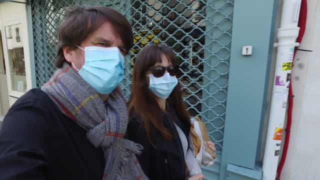woman and a man, with a protective mask, walking on the street, on may 13, 2020 in paris, france. france has started a progressive relaxation of its... - two parents stock videos & royalty-free footage