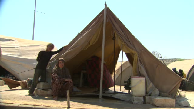 a woman and a young boy stand beside a tent in syria during the syrian civil war - (war or terrorism or election or government or illness or news event or speech or politics or politician or conflict or military or extreme weather or business or economy) and not usa stock videos & royalty-free footage