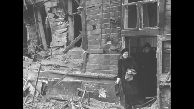 woman and another person standing in doorway of building demolished by bombs / same woman wearing fur coat and hat standing in front of building... - winter coat stock videos & royalty-free footage