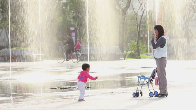ls woman and baby playing on square/xian,shaanxi,china - sportkinderwagen stock-videos und b-roll-filmmaterial