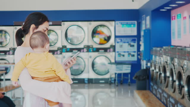 woman and baby waiting when washing is over in laundromat - launderette stock videos & royalty-free footage