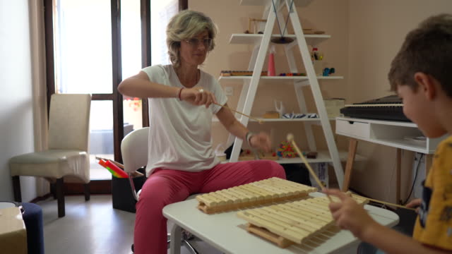 woman and boy having fun during music therapy at rehabilitation center - invisible disability stock videos & royalty-free footage