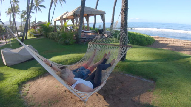vidéos et rushes de a woman and boy, mother and son, lying in a hammock at beach in kaanapali, maui, hawaii. - slow motion - se reposer