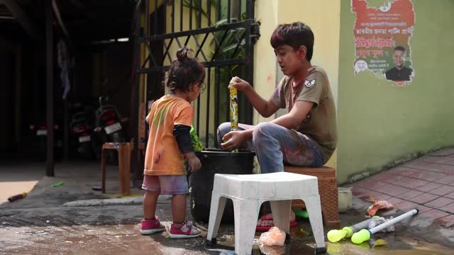 woman and child celebrating holi in front of their apartment amid covid-19 pandemic on march 28, 2021 in guwahati, india. the holi festival is... - multi coloured stock videos & royalty-free footage